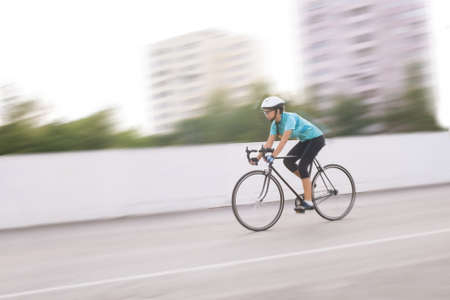 panning shot: portrait of young professional female athlete racing on a bike. motion blurred image.horizontal orientation Stock Photo