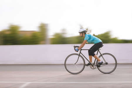 panning shot: portrait of young professional female athlete racing on a bike  motion blurred image horizontal orientation