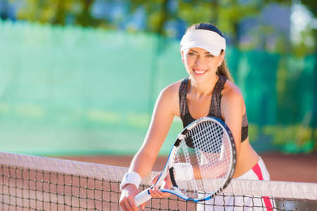 lawn tennis: Portrait of positive looking female tennis athlete with racquet standing at clay court. horizontal image