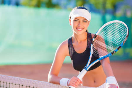 Lovely portrait of beautiful caucasian sportswoman holding a tennis racket at the court and smiling. horizontal shot photo