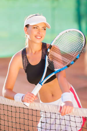 Lovely portrait of beautiful caucasian sportswoman holding a tennis racket at the court and smiling. vertical shot photo