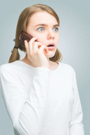 exclaim: natural portrait of caucasian teenage girl with mobile phone. isolated on gray. vertical shot Stock Photo