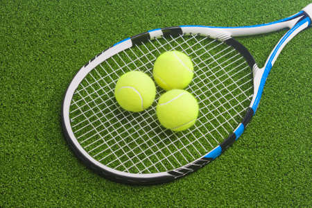 Tennis racket with three balls lies on a green lawn surface. tennis concept.horizontal image