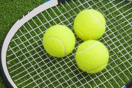 raquet: Three tennis balls lie on a tennis racket strings. over green lawn surface. tennis concept.horizontal image Stock Photo