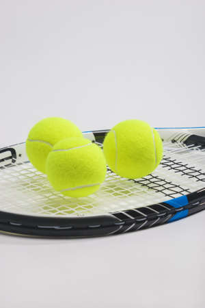 Tennis racket and three green balls on white background. vertical image photo