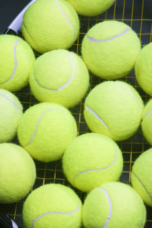 raquet: Plenty of tennis Balls on Raquet Strings against Black background. Vertical Image