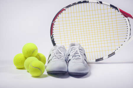 raquet: Sports Images Concepts: Tennis Raquet, Tennis Balls and Trainers against gray. Horizontal Image