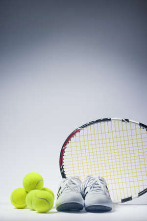 raquet: Sports Images Concepts: Tennis Raquet, Tennis Balls and Trainers against gray. vertical Image