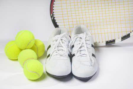 Tennis sports Concept: Raquet, Balls and Sneakers against white. Horizontal Image Stock Photo