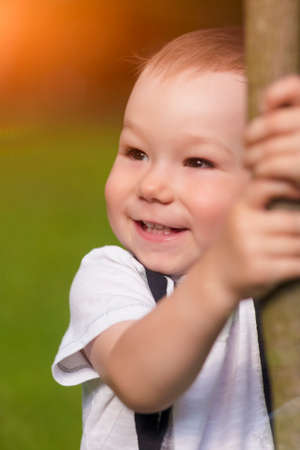 sincere: Portrait of Smiling Little Boy Outside. Vertical Shot Stock Photo