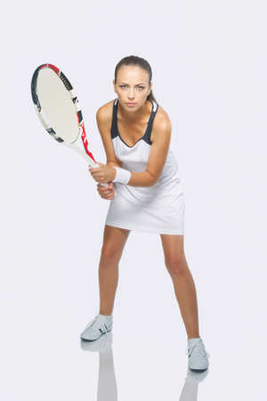 Portrait of Female Caucasian Sportswoman in Professional Outfit Preparing To Serve Ball. Isolated on White. Vertical Image photo