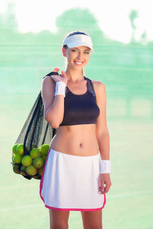 Professional Tennis Athlete with a Plenty of Tennis Balls Standing on Court. Vertical Image photo