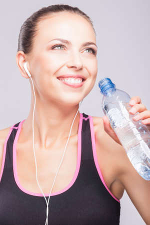 Portrait of Sporty fit woman drinking water, isolated against gray background. Vertical Image photo