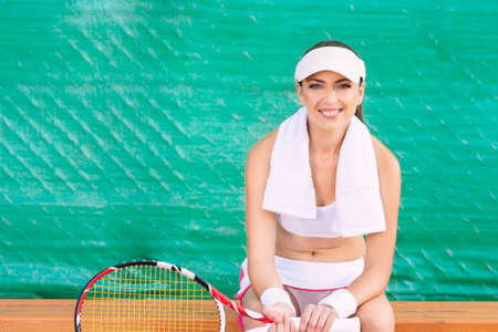 player bench: Positive Looking Professional Female tennis Player having rest on Bench of Tennis Court and Smiling. Horizontal Image