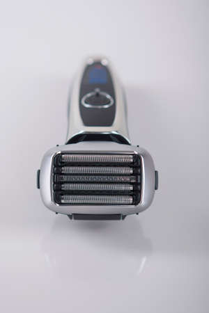 raze: Ultramodern Five Blades Electric Shaver On Smooth Reflecting Surface. Vertical Image Stock Photo