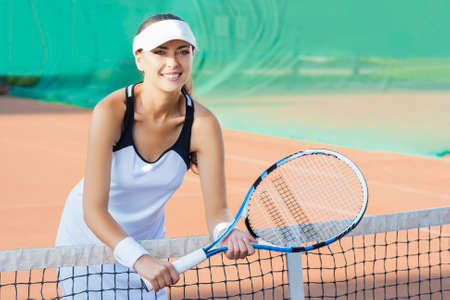 Portrait of Happy Smiling Female Tennis Player at Court Standing Close To the Net. Horizontal Image