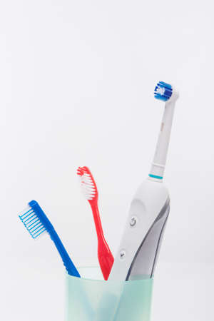 Electric and Manual Toothbrushes in One Cup Together. Isolated Over White Background. Vertical Image Stock Photo