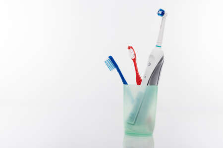 Electric and Manual Toothbrushes in One Cup Together. Isolated Over White Background. Horizontal Image