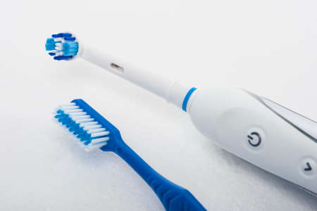 Traditional Manual and Electric Toothbrush Together Over White. Horizontal Image
