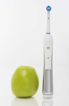 hygien: Dental Hygien Concept: Green apple Together With Electric Toothbrush. Over White Background. Vertical Image Stock Photo