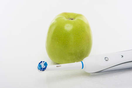 hygien: Dental Hygien Concept: Green apple Together With Electric Toothbrush. Over White Background. Horizontal Image