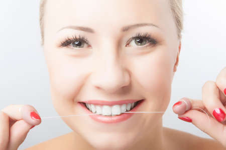 Caucasian Woman Flossing Teeth and Smiling. Dental Care and Oral Hygiene Concept. Horizontal Image