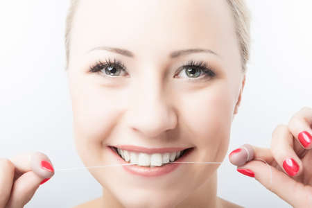 cary: Caucasian Woman Flossing Teeth and Smiling. Dental Care and Oral Hygiene Concept. Horizontal Image