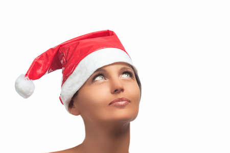 Happy Sensual Brenette Woman in Santa Hat Looking up. Isolated Over White  photo