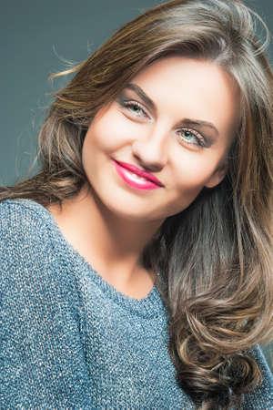 dishevel: Primo piano ritratto di una giovane e bella donna con capelli marroni lunghi e Fashion Make up sorridente. Contro Gray. Immagine verticale