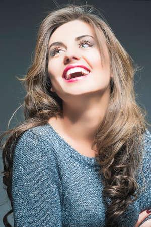 dishevel: Felice Ridendo Bella giovane donna con Natural Brown capelli lunghi e Vivid make up. Contro Gray. Immagine verticale
