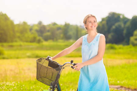 blondy: Happy Beautiful Caucasian Blond Having a Stroll in the Park Area With Her Bicycle.  Stock Photo