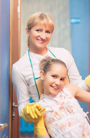 Mother and Daughter doing Tidy Up Together. Indoors Shoot. Vertical Image photo