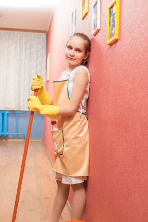 Portrait of Little Teenage Girl With Mop In Front of the Kitchen. Vertical Image photo