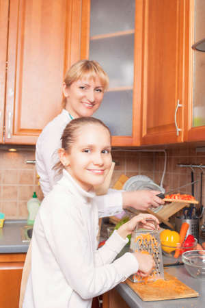 Positive Caucasian Family Preparing Food Together and Having Good Time  Vertical Image photo