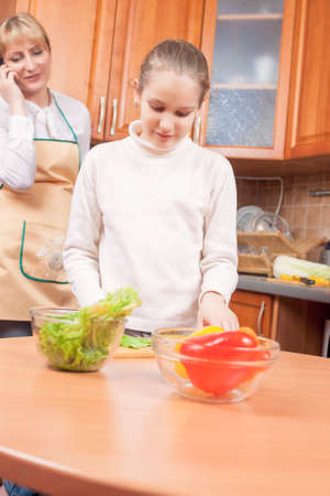 Mother Teaching Her Teenage Daughter How to Cook and Standing Behind  Vertical Image photo
