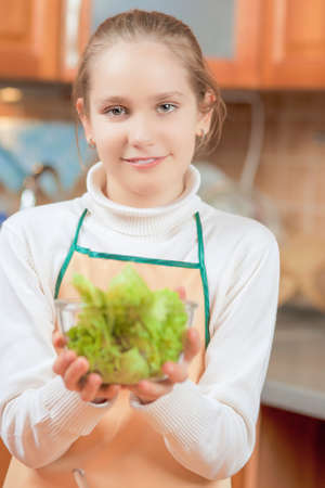 Happy Smiling Teenage Girl Demonstrating Her Speciallty in the Kitchen  Vertical Image photo