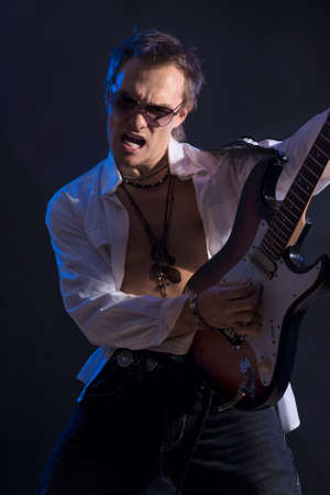 Portrait of Male Guitarist Playing with Expression. Vertical Image
