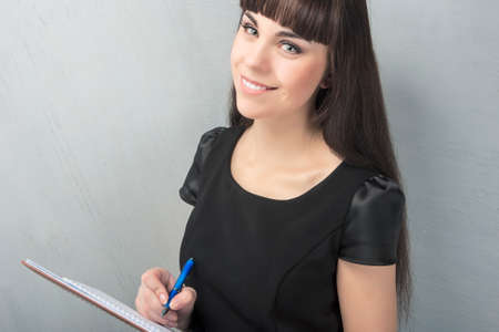 Smiling Happy Brunette Woman Writing Notes. Horizontal Image