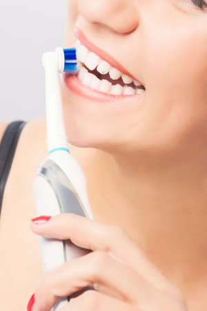 Dental Hygiene: Blond Woman Mouth Closeup while Brushing Teeth with Electric Toothbrush. Vertical Image Stock Photo