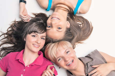 dental smile: Portrait of Happy Caucasian Girls Wearing Teeth Braces Lying Together with Heads In Center. Horizontal Image