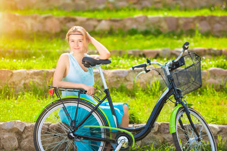 blondy: Beautiful Blond Woman Outdoors Enjoying Nature with Bicycle. Beautiful young Blond Lady at the Green Field. Horizontal Image