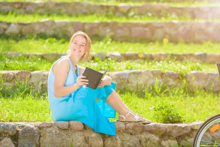 Portrait of  Young Caucasian Blond Woman Reading Digital eBook Outdoor.Sitting Against Green Grass. Horizontal Image photo