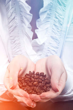 Hands Closeup with coffee beans. Vertical image orientation photo