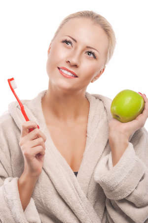 Blond Woman in Dressing Gown Cleaning Teeth with Manual Toothbrush. Over White Background. Vertical Image photo