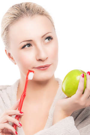 Portrait of Thoughtful Blond Woman in Dressing Gown Holding Green Apple Prior to Her Teeth Cleaning with Manual Toothbrush. Isolated Over Pure White Background. Vertical Composition photo