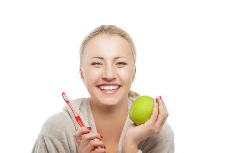Portrait of Young Laughing Blond Woman in Dressing Gown Holding Green Apple and  Manual Toothbrush in Hands. Isolated Over Pure White Background. Horizontal Composition photo