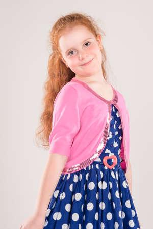polka dotted: Retrato de feliz pelirroja cauc�sica desgasta de la muchacha punteada polca vestido. Contra el fondo blanco. Vertical de la imagen
