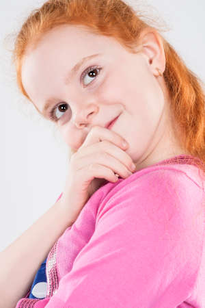 Closeup Portrait of Caucasian Beautiful Curious Redhaired Little Girl. Looking Up Against White Background. Vertical Image photo