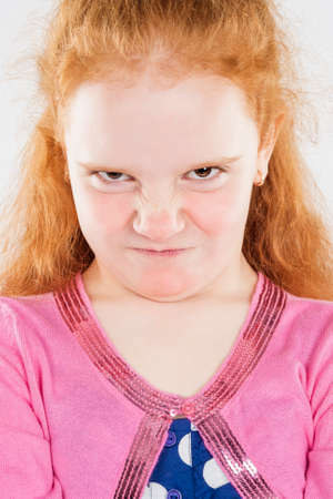 Portrait of Angry and Furious Little Caucasian Redhaired Girl. Standing Against White Background. Vertical Shot photo