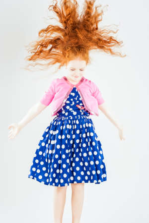 Happy Jumping Red-haired Caucasian Girl In Polka-Dotted Dress Playing With Her Long Hair. Against White Background. Vertical Image Composition photo